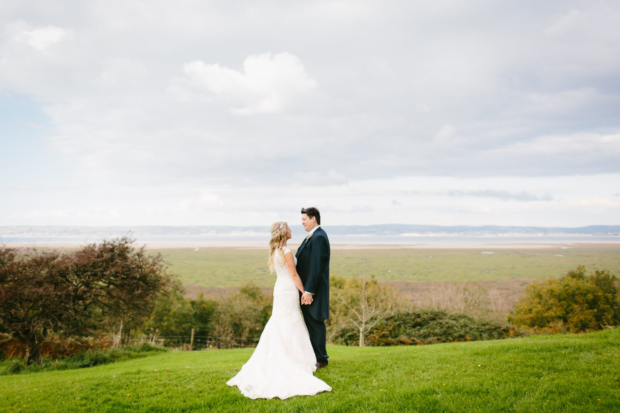 Overlooking the North Gower Coastline. Bride and Groom, loving look. Holding hands. Perfectly peaceful wedding